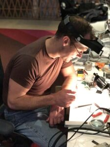 Engineer Dave Hayden at a desk, with welder's goggles pushed up on his head, working on Playdate