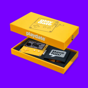 """An image of Playdate in its box with the lid hovering above, so you can see the top of the box and how Playdate is packed inside. A card covering the USB-C cord reads, """"have fun!"""" in a speech bubble."""