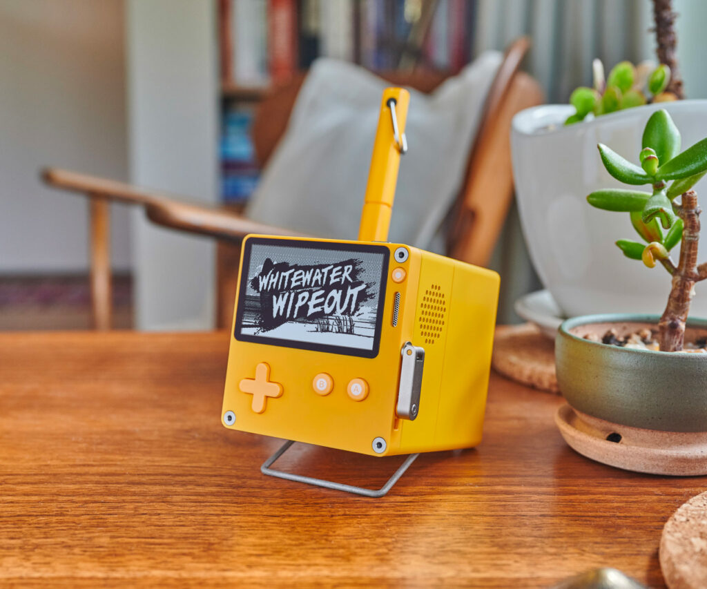 A Playdate attached to a stereo dock sits on a side table in a living room, next to a potted succulent. The Playdate screen is displaying the title screen from the game Whitewater Wipeout. The yellow pen included with the dock rests in the pen holder.