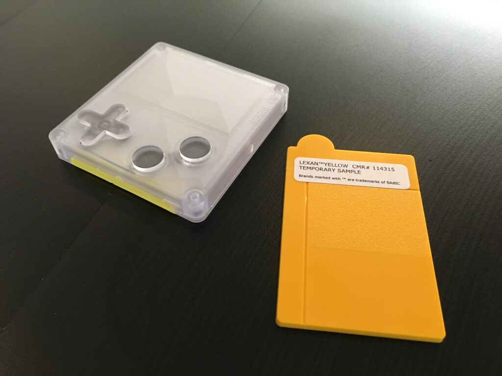 A transparent plastic Playdate case next to a rectangular piece of yellow plastic with a sticker reading Lexan yellow CMR# 114315 Temporary Sample